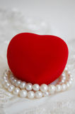 Red Heart and Pearl Necklace. Pearl necklace and a closed heart-shaped jewelry box on lace Stock Photos
