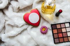 Red heart, perfume, lipstick, eye shadow and a candle on a white blanket stock images