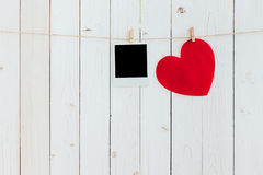 Red heart and photo frame blank hanging at clothesline on wood w Royalty Free Stock Photo