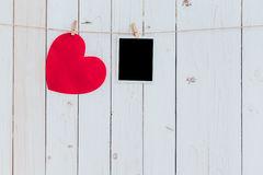 Red heart and photo frame blank hanging at clothesline on wood w Stock Photography