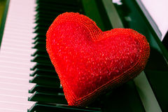 Red heart on piano keyboard. Red heart on the top of piano keyboard Stock Image