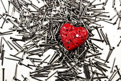 Red heart on pile of iron nails, pierced by a nail and holes in Royalty Free Stock Photo