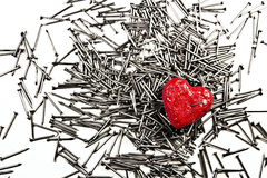Red heart on pile of iron nails, pierced by a nail Royalty Free Stock Photo