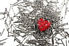 Red heart on pile of iron nails, pierced by a nails Stock Image