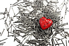 Red heart on pile of iron nails, pierced by a three nails Royalty Free Stock Photography