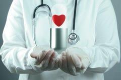Red heart pill inside capsule as medical concept. Doctor scientist shows red heart pill inside capsule as medical concept stock image