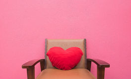 Red heart pillow on the chair wall pink background . Stock Photo