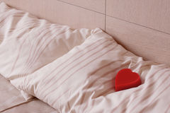 Red heart on pillow. Love and romance symbol. Stock Photos