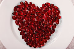 Red heart pills. Red heart shaped pills on a white plate Royalty Free Stock Images
