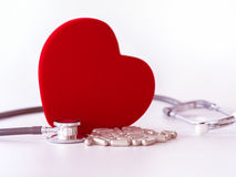 Red heart, pills  and stethoscope on white background. health care concept. Stock Photos