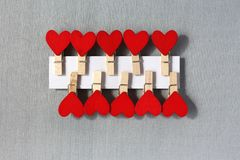 Many red hearts with clothespin. A red heart with a pin the Image of Valentine`s day Royalty Free Stock Photos