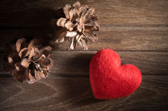 Red heart with pine cone on wood table. Royalty Free Stock Photo