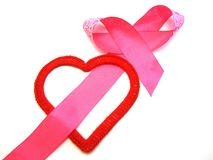 Red heart with a pink ribbon. Red heart intertwined with a pink ribbon royalty free stock images