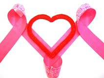 Red heart with a pink ribbon. Red heart intertwined with a pink ribbon royalty free stock photos