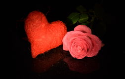 Red heart and pink rose on black sparkling reflective surface Stock Photos