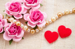 Red heart and pink rose on fabric background. Royalty Free Stock Image