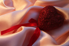 Red heart on pink silk for St Valentine's day Royalty Free Stock Photo
