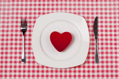 Red heart on plate. On red gingham Stock Photos