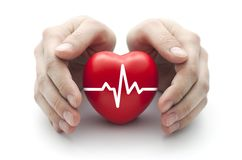 Red heart with pulse covered by man`s hands. Small red heart with pulse covered by man`s hands stock photos
