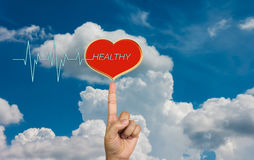 Red heart with pulse or heart beat and text healthy with hand on. Sky royalty free stock photography