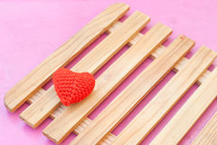 Red heart. Put on wood panel on the pink table Royalty Free Stock Images