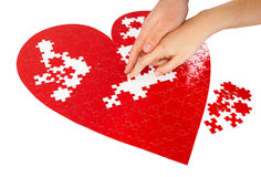 Red heart puzzles. Young couple assembling a red puzzle heart shape on white background Royalty Free Stock Photos