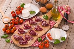 Red heart r.avioli with tomato, mozzarella and basil. Red heart ravioli with tomato, mozzarella and basil on cutting board royalty free stock photos
