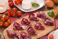 Red heart r.avioli with tomato, mozzarella and basil. Red heart ravioli with tomato, mozzarella and basil on cutting board stock images