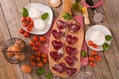Red heart r.avioli with tomato, mozzarella and basil. Red heart ravioli with tomato, mozzarella and basil on cutting board royalty free stock image