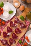 Red heart r.avioli with tomato, mozzarella and basil. Red heart ravioli with tomato, mozzarella and basil on cutting board royalty free stock photo