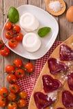 Red heart ravioli with tomato, mozzarella and basil. stock photography