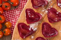Red heart ravioli with tomato, mozzarella and basil. royalty free stock image