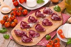Red heart ravioli with tomato, mozzarella and basil. royalty free stock photo