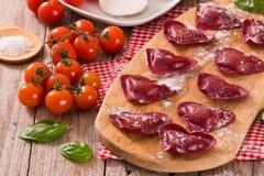 Red heart ravioli with tomato, mozzarella and basil. stock image