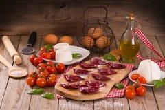 Red heart ravioli with tomato, mozzarella and basil. stock photo
