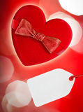 Red heart with red bow. And blank tag, defocused lights on backgr Royalty Free Stock Photos