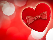 Red heart with red bow. Defocused lights on background Royalty Free Stock Photo