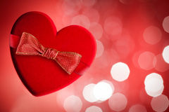 Red heart with red bow. Defocused lights on background Royalty Free Stock Photography