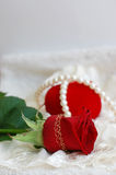 Red Heart, Red Rose Pearl Necklace. Pearl necklace, red rose, and a closed heart-shaped jewelry box on lace Royalty Free Stock Photos
