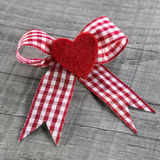 Red heart with a red white checked ribbon for valentines day. Stock Image