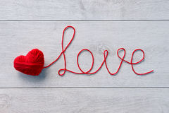 Red heart of red wool yarn. On a wooden background. Valentines Day background stock image