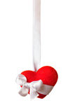 Red heart with a ribbon isolated on white. Single red heart with bow hanged on the white satin ribbon isolated on white background (with clipping path Stock Photo