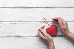 Red heart on a ribbon and female hands, white wooden plank background. Valentine`s Day.Top view, copy space stock photography