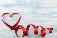 Red heart of ribbons on a blue wooden background. place for text. Valentine`s Day royalty free stock photos