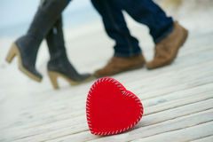 Red heart on the road with man`s and woman`s feet. Heart on the road with man`s and woman`s feet royalty free stock photography