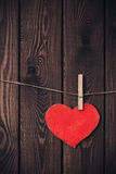 Red heart on a rope with clothespin on a wooden background. Copy space. Vertical Royalty Free Stock Image