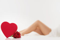 Red heart and a rose in front of legs Royalty Free Stock Photo
