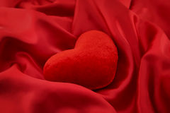 Red heart on satin background. Royalty Free Stock Photo