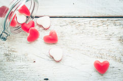 Red heart shape candy in a glass jar. On a white rustic wooden table with space for text. Romantic love concept. Valentine`s Day greetings card. Valentines stock photos