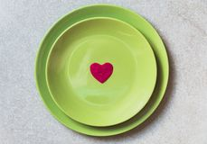 A red heart shape in the center of green plates on the grey background. Flat lay stock images